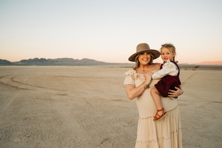 Mother holds her little daughter in her arms for beautiful desert sunset family photos captured by las vegas family photographer hayway films