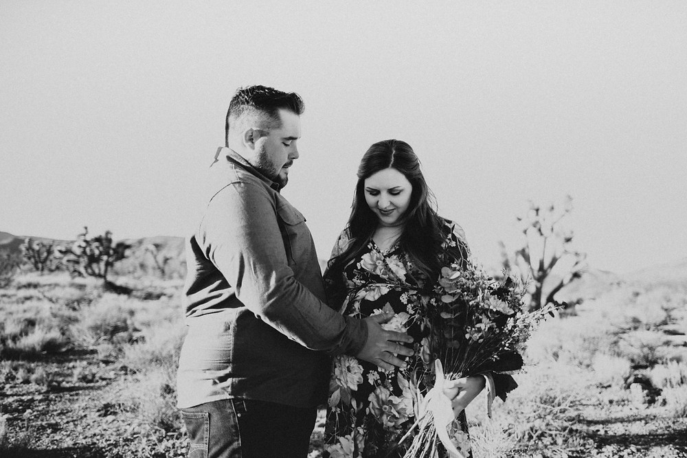 Man and wife pose in the desert during their las vegas maternity photos