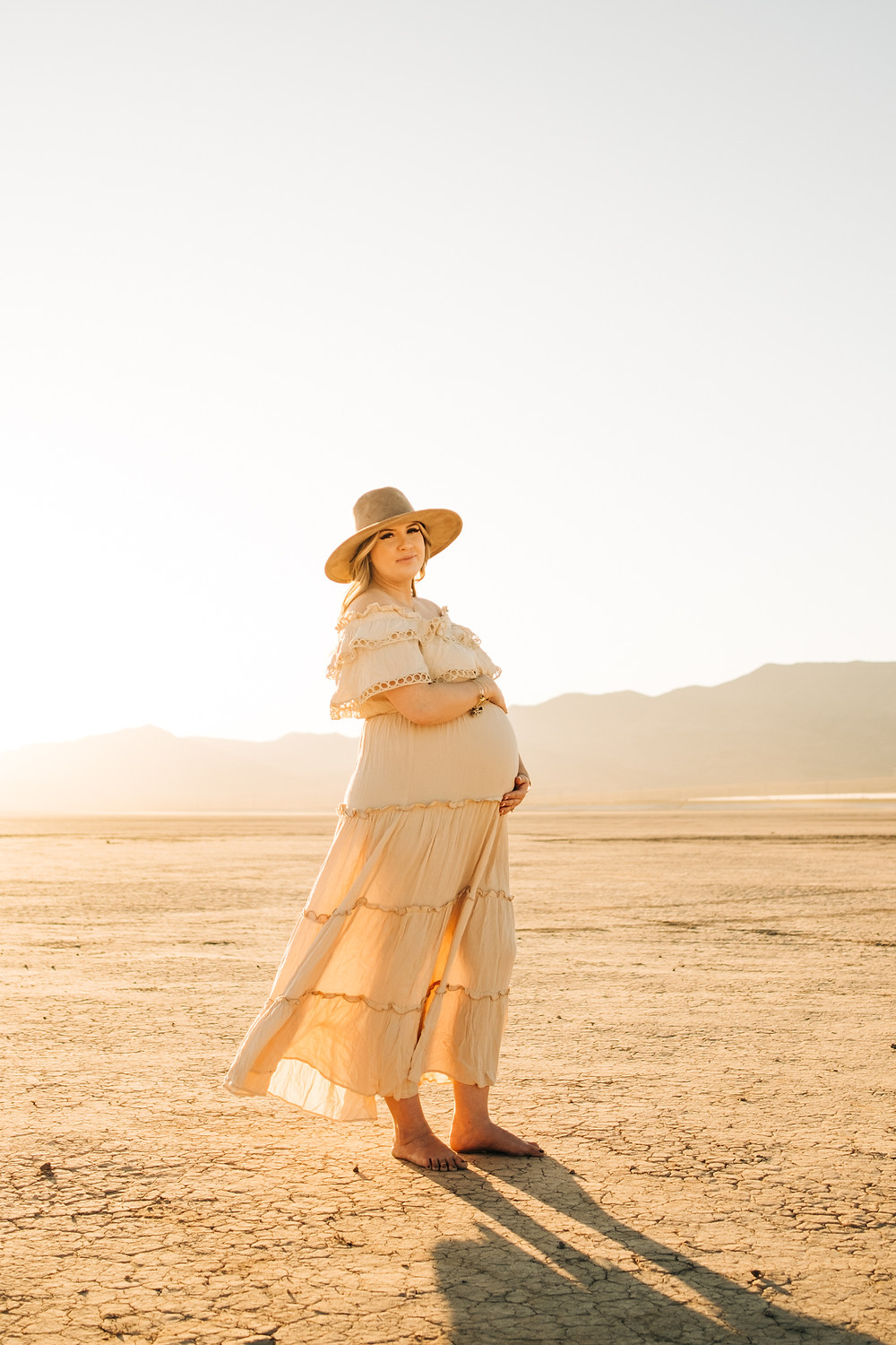 Gorgeous blonde mother sits on the dry lake bed outside of las vegas nevada at sunset holding her pregnant belly. beautiful glowing maternity pictures captured by las vegas maternity photographer hayway films