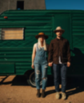 Blonde woman wearing blue denim overalls, brown leather boots a wide brimmed brown hat stands straight with a serious face. She is holding hands with a man wearing a brown jacket, tan hat, and cream clarks shoes. They both have serious faces and are in Joshua Tree california, standing in from on a vintge green camper in the middle of the day.
