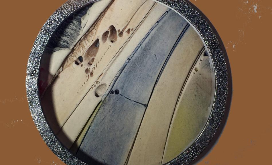 Isolating and incorporating ceramic within a rim of shibuichi.
