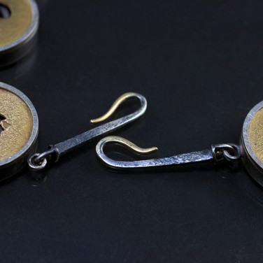 These hooks attach to the brooch and become the claso when the neckpiece is worn alone.