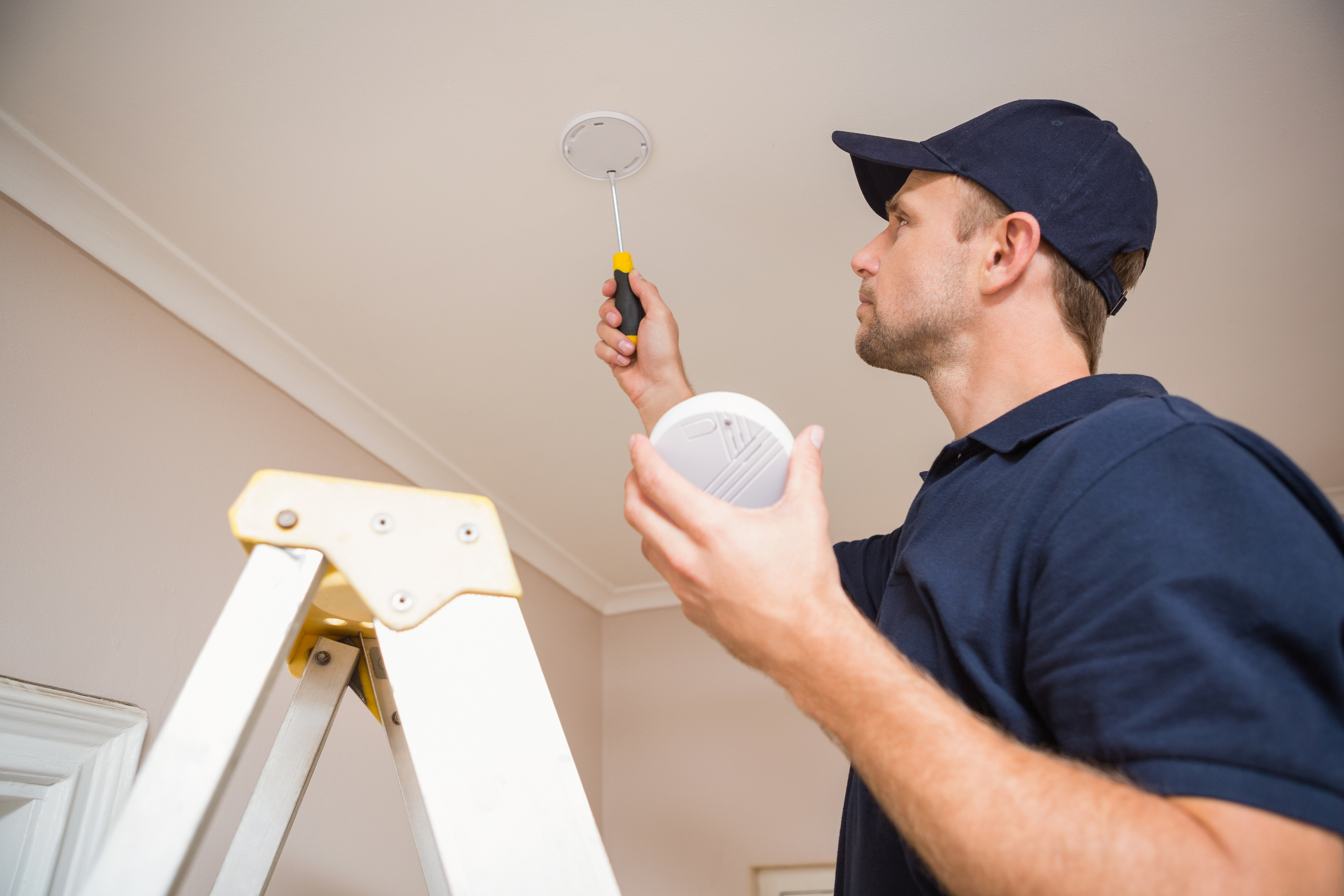 Handyman installing smoke detector with screwdriver on the ceiling.jpg