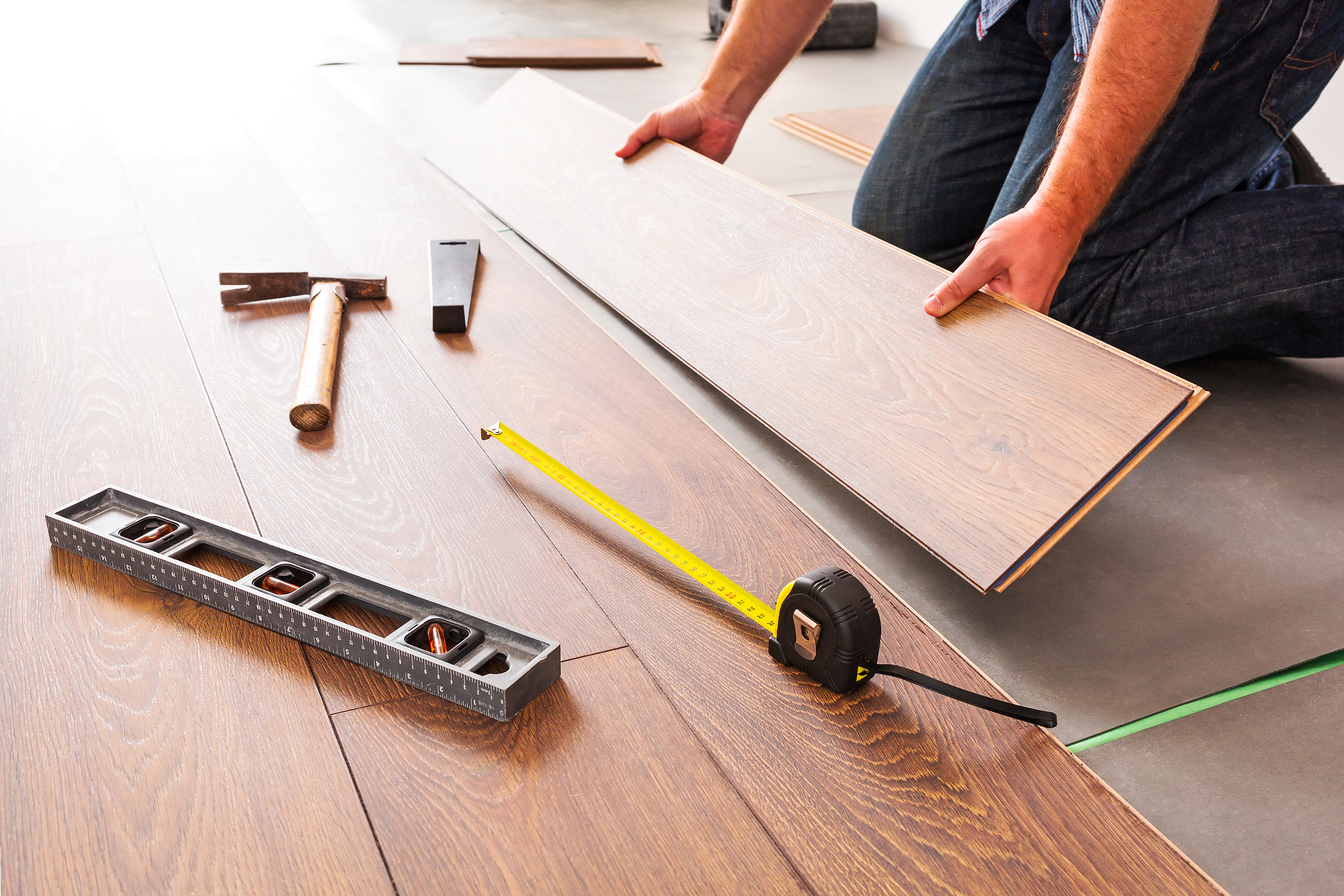 Man installing new laminated wooden floor.jpg
