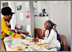 19 Jessica Huntley (answering enquiry) at Bogle-L'Ouverture Publications bookstall. c2000s.  Huntley