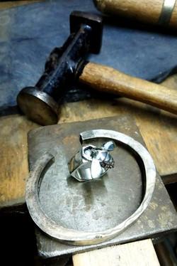 Hammer and jewellery on jewellery benchpeg