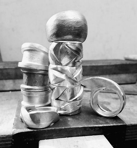 Stack of chunky silver rings on jewellery workbench