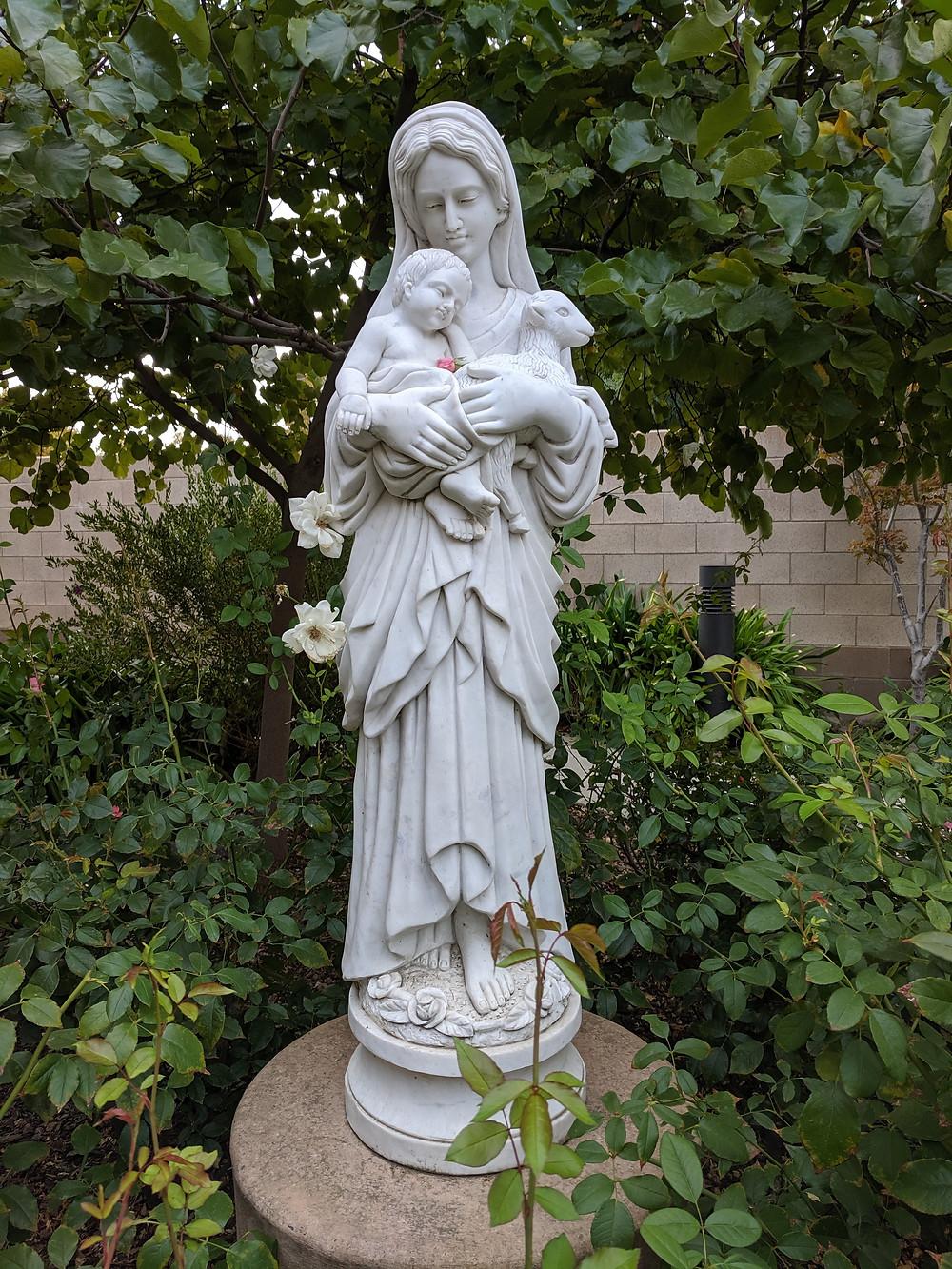 Estatua de Nuestra Señora del Buen Pastor rodeada de rosales.