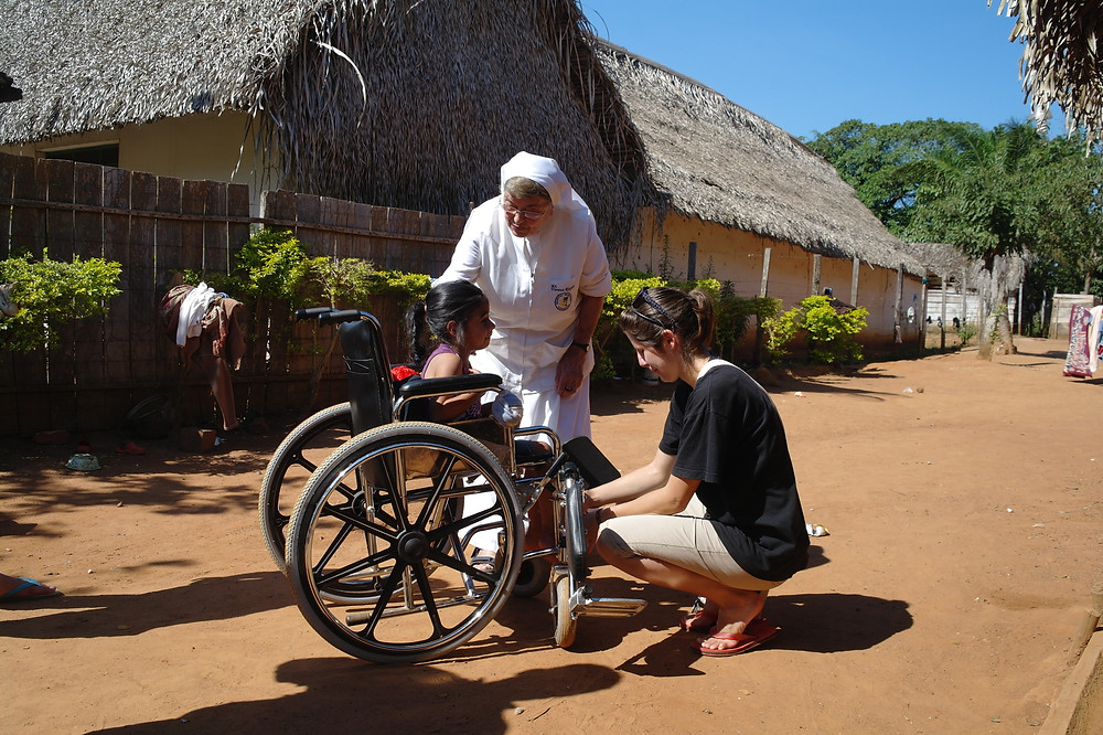 a girl on a wheelchair, a nun looking at her, and a lady adjusting the girl's legs
