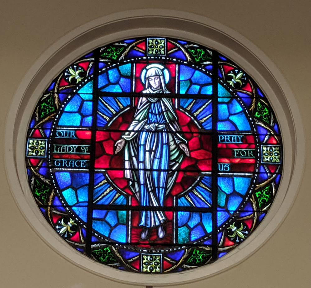 a circular stained glass window of Our Lady of Grace