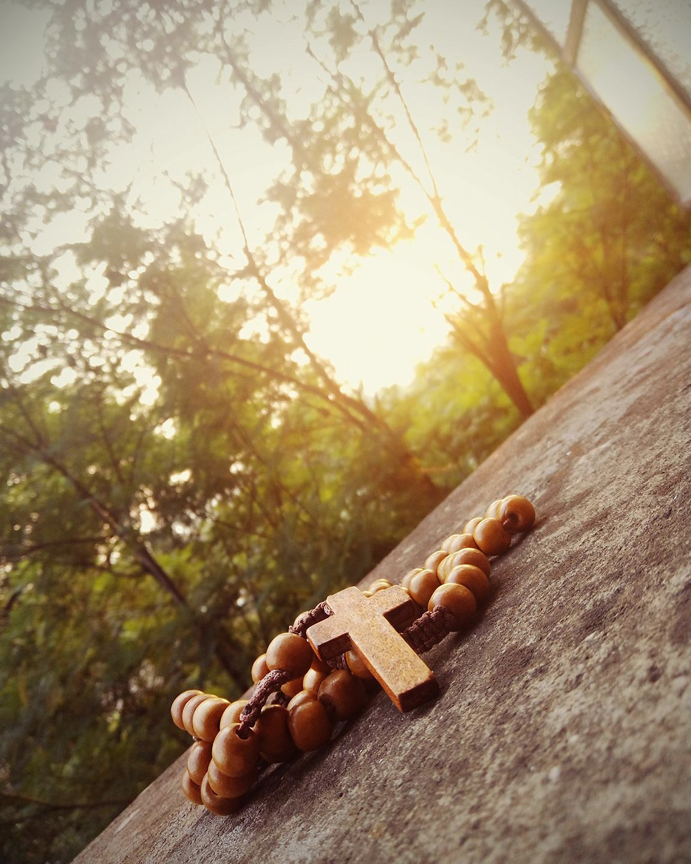 a wooden rosary on a stone