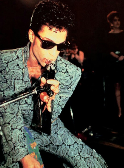 Prince on stage wearing paisley print suit