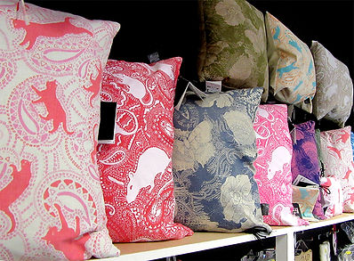 paisley cushions with cat rat butterfly patterns displayed on shelves