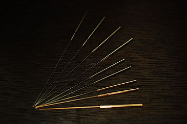A photograph of nine silver acupuncture needles, four longer than the other five. They're arranged into a quarter-circle with their tips touching and handles evenly spaced against a dark brown wood grain background.