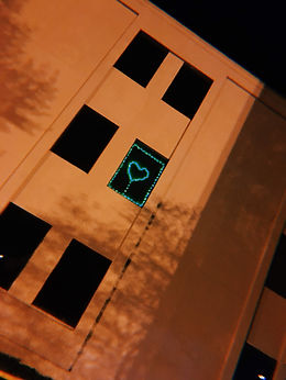 A photograph of the exterior of the office building. It's night and the sky and windows are dark, the exterior of the building a brown color. In one window, green lights are arranged into a heart shape and frame around the window.