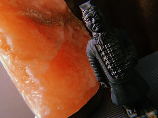 A photograph on an angle, showing a pink salt lamp that is not lit. Next to the lamp is a small replica of a terra cotta warrior from China. It is black with a rusty patina.