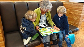 grandma reads to grandkids, grandparents, elderly woman and kids having fun