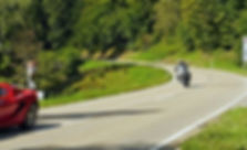 motorcycle rider in the mountains with red sports car