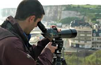 A man looks at the view of the city below through a spotting scope