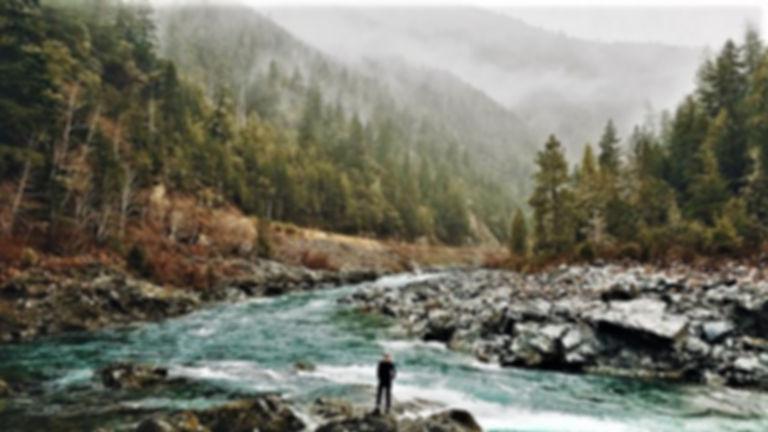 Man walking in beautiful mountain wilderness creek