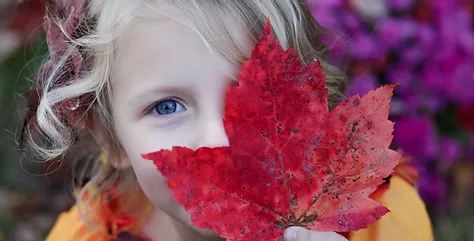 cute girl with big red autumn leaf