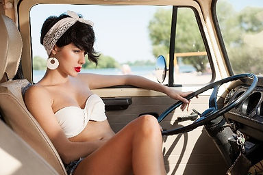 Beautiful woman in the driver seat of vintage car, summer