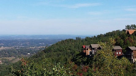 Several cabins on a mountainside in Pigeon Forge overlooking Sevierville and the town below