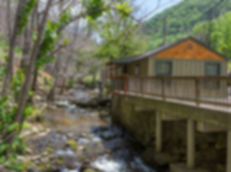 Roaring Fork Cabin exterior showing cabin and creek
