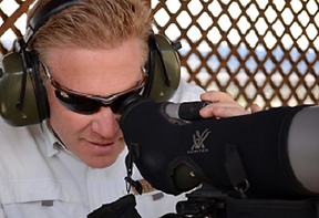 Example of eye relief. Man wearing glasses looks into spottin scope