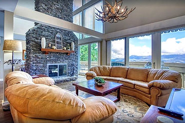 Bighorn Chalet rental in Gatlinburg interior view with stacked stone fireplace and large windows with mountain view