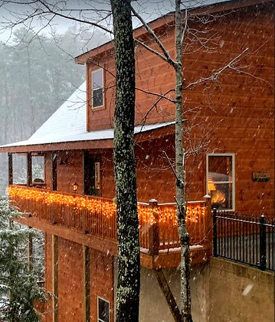 Bearadise, cabin near The Island in Pigeon Forge, Tennesee. Shown exterior in falling snow and decorated for Christmas