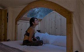 Inside an Under Canvas tent, a girl looks through the window on top of the tent to see the stars