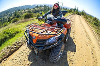 Woman sits on an ATV on a dirt road