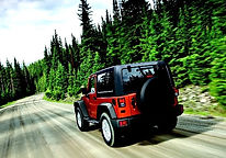 Red Jeep driving through the mountains