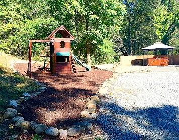 Gatlinburg Cabin named Queen of Gatlinburg, exterior view of kids playground amenities and hot tub