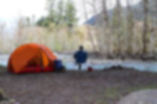 Campsite wth tent on a creek in the mountains. Person fishing in creek.