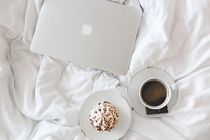 Laptop, coffee, cupcake, breakfast in bed at hotel