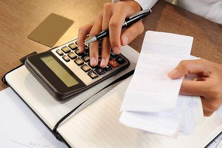 closeup-person-holding-bills-calculating