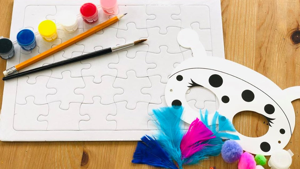Craft pack with jigsaw puzzle, a mask, paint, pencil, paint brush and feathers