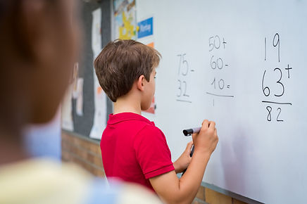 Rear view of young boy solving addition