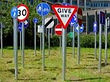 A collection of signs. Give way signs, 30 limit, pedestrian and bike signs, national speed sign.