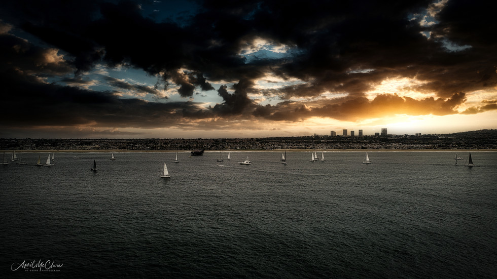 Early morning dramatic, dark sunrise on the water with yachts in the background, Newport Beach, California Aerial Photograph