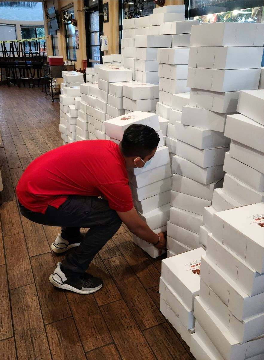 Employee stacking columns of to-go food orders