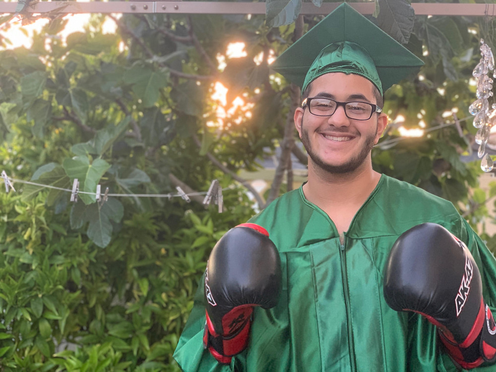 Smiling youth with boxing gloves and graduation robe