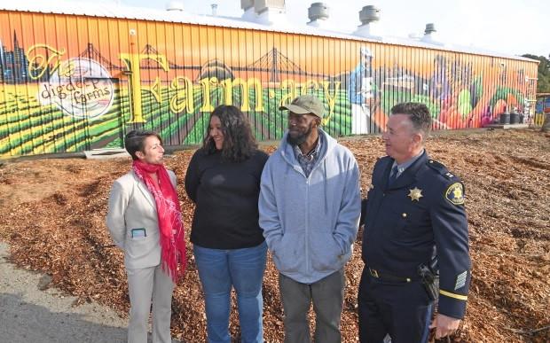 DSAL staff standing by Dig Deep Farms Food Hub Mural