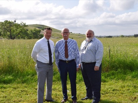 Supervisors standing on new farmland