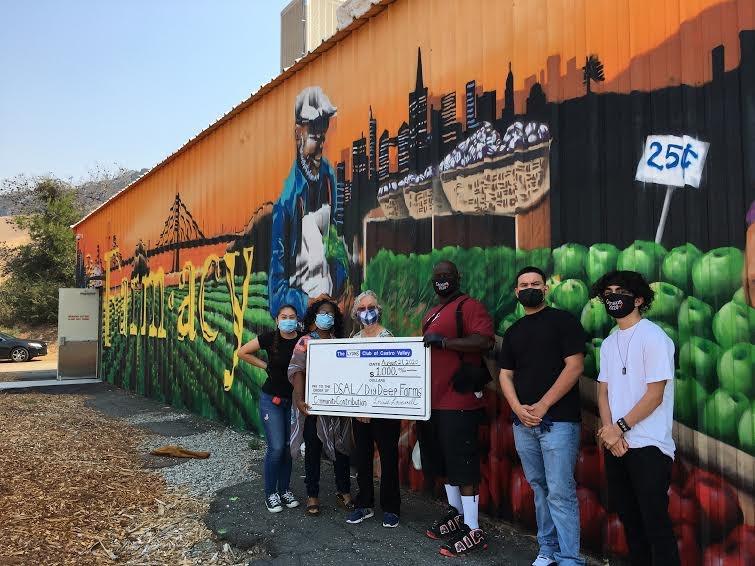 Team members in front of Dig Deep Farms Mural