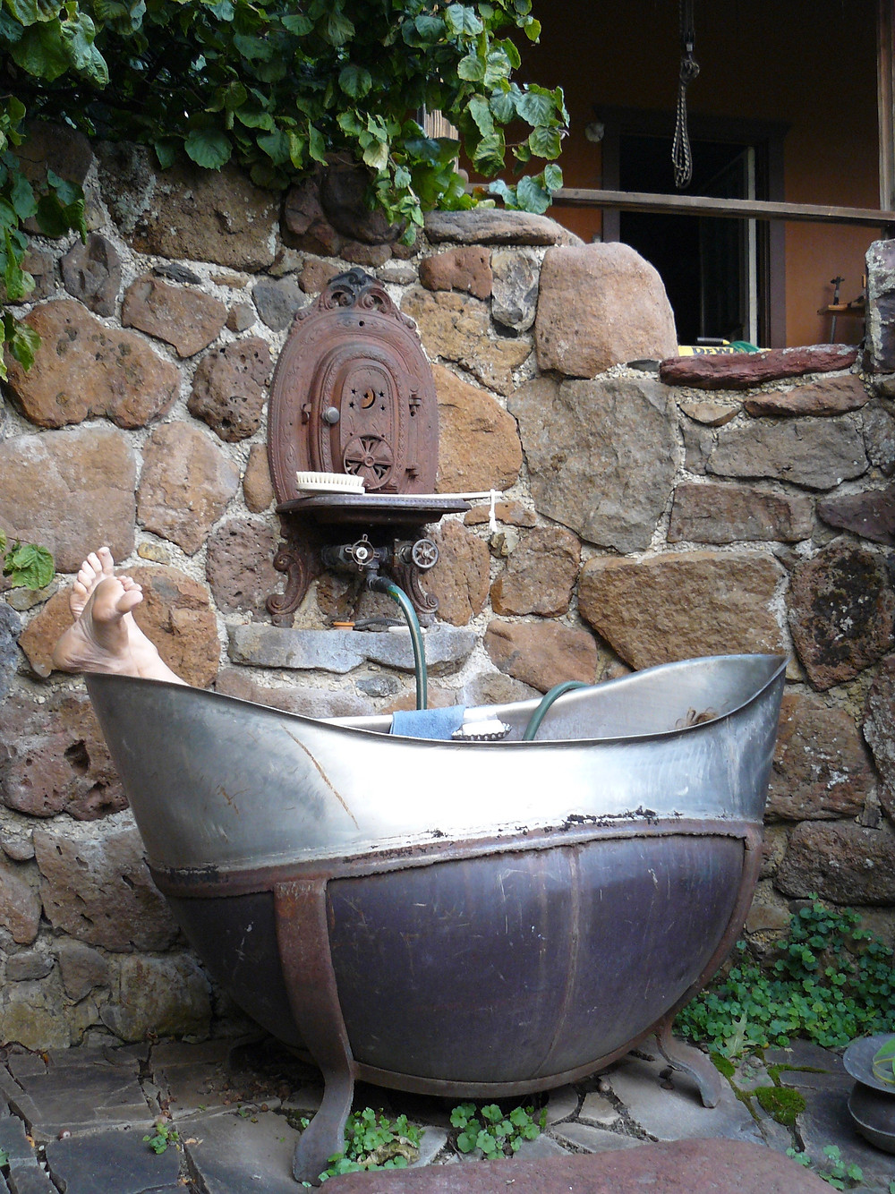 A pea pod shaped tub in a stone walled grotto that has an old wood stove front set into the wall  and 2 feet are sticking out one end of the tub.