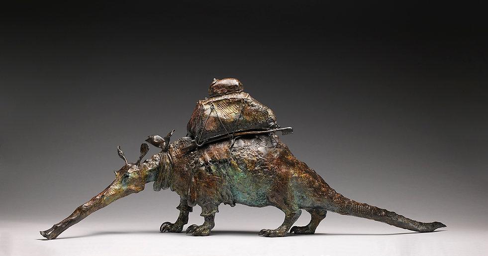 Bronze aardvark sculpture with suitcase, toothbrush and neckerchief.