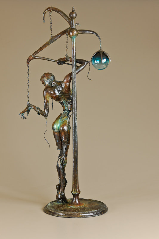 Back view of a bronze female nude sculpture of a marrionette puppet hanging from a lamppost who controls herself.
